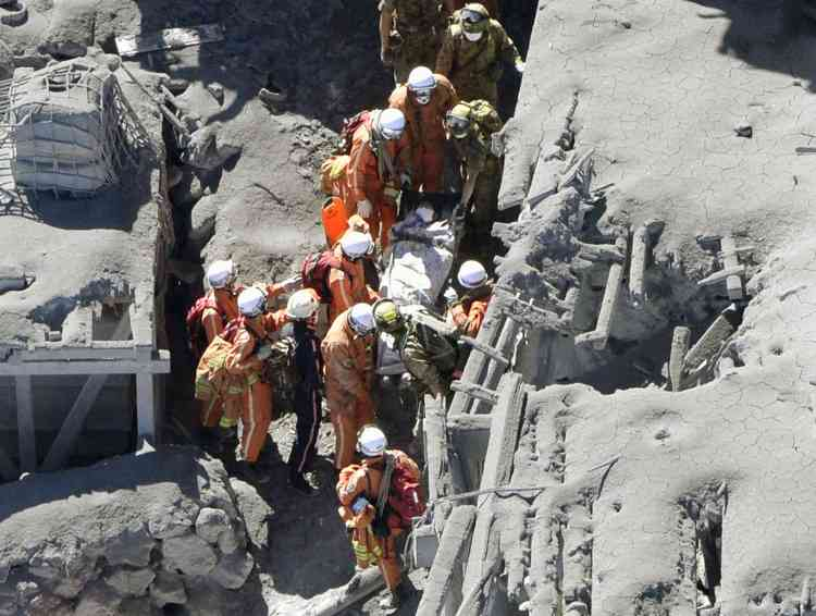 Japan Self-Defense Force (JSDF) soldiers and firefighters carry an injured person among mountain lodges, covered with volcanic ash, near a crater of Mt. Ontake, which straddles Nagano and Gifu prefectures in this September 28, 2014 photo taken and released by Kyodo. More than 500 Japanese military and police set out on Sunday to search the peak of a volcano popular with hikers a day after its sudden eruption trapped hundreds on the mountain for hours, amid conflicting reports about missing and injured climbers.   Mandatory credit.   REUTERS/Kyodo (JAPAN - Tags: DISASTER ENVIRONMENT SOCIETY)  ATTENTION EDITORS - THIS IMAGE HAS BEEN SUPPLIED BY A THIRD PARTY. THIS PICTURE WAS PROCESSED BY REUTERS TO ENHANCE QUALITY. AN UNPROCESSED VERSION WILL BE PROVIDED SEPARATELY. MANDATORY CREDIT. JAPAN OUT. NO COMMERCIAL OR EDITORIAL SALES IN JAPAN. YES