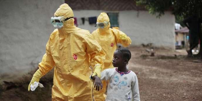 Une enfant présentant des symptômes d'Ebola accompagnée par un soignant, au Liberia.