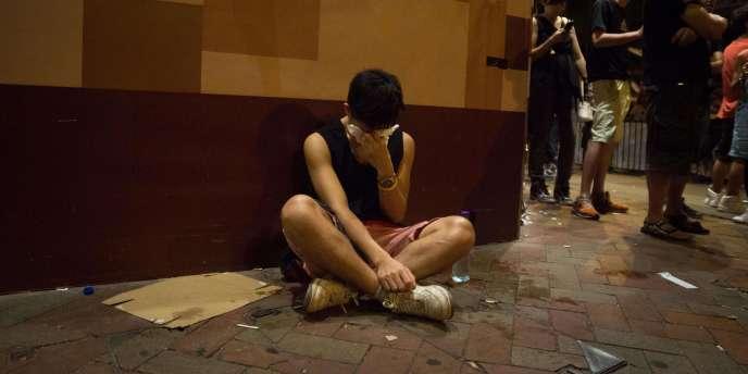 Un manifestant se couvre les yeux après avoir reçu des tirs de bombes au poivre.