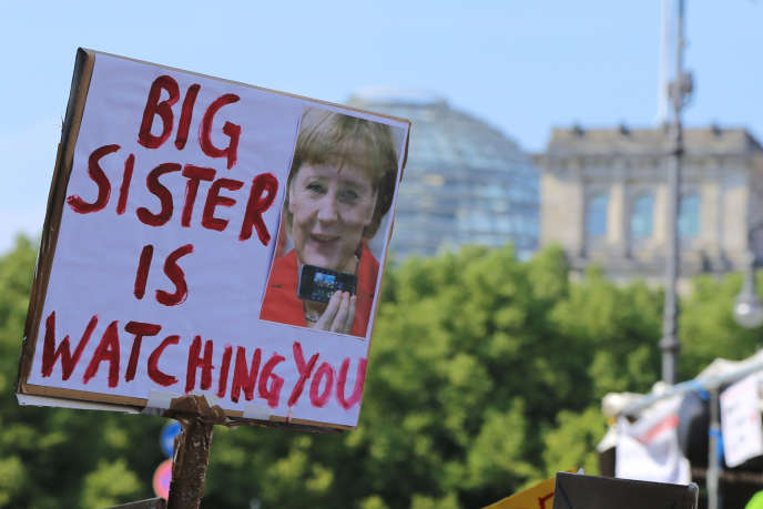Un manifestant brandit une pancarte dénonçant l'attitude d'Angela Merkel lors d'une manifestation contre la surveillance à Berlin, en juillet 2013.