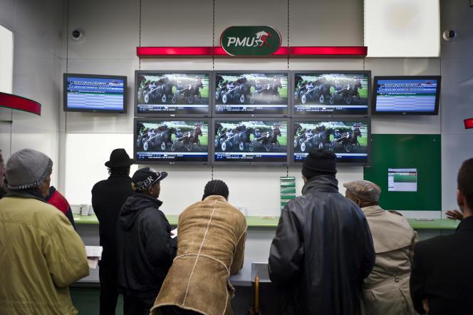 Des joueurs suivent une course dans une boutique du PMU à Lyon.