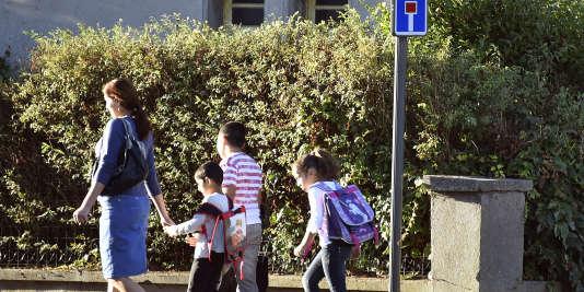 Une mère de famille accompagne ses enfants à Albi, en septembre 2014.