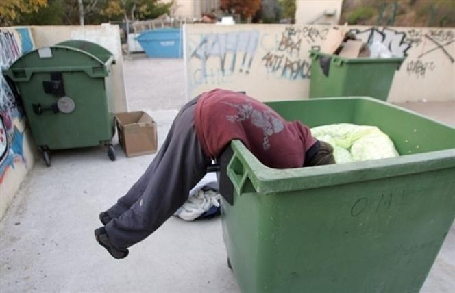 Un homme cherche de quoi manger dans une poubelle à Aix-en-Provence.
