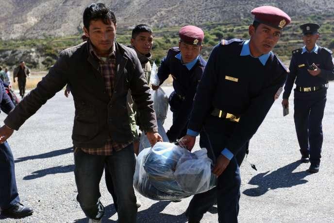 Des policiers népalais transportent le corps d'un trekkeur tué dans la tempête de neige qui s'est abattue sur l'Himalaya le 14 octobre 2014.