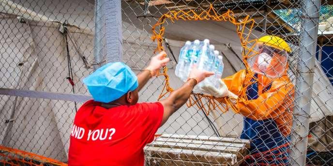 Transmission de bouteilles d'eau dans un centre de traitement du virus Ebola à Freetown.