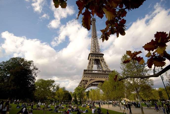 Les Parisiens profitent du soleil au pied de la tourEiffel, le 19octobre2014.