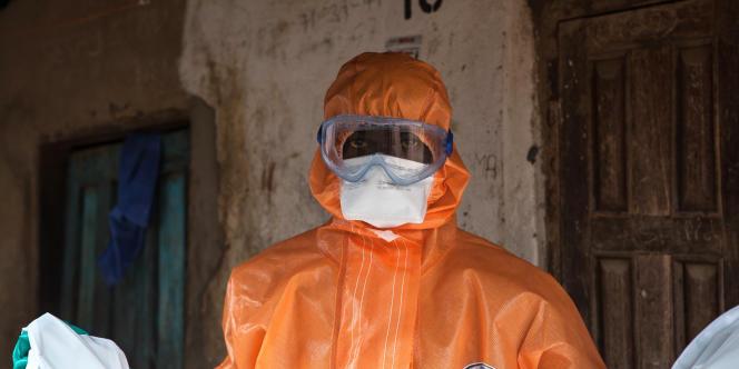 Un homme désinfecte une maison près de Freetown, au Sierra Leone, durant l'épidémie d'Ebola.
