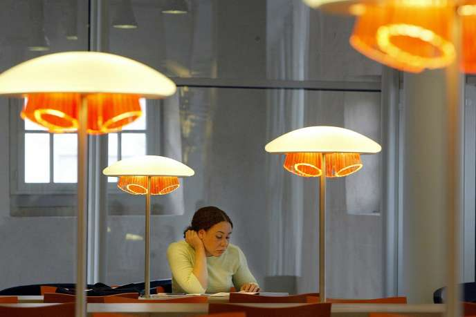 une jeune femme consulte un ouvrage de la grande bibliothèque de Marseille.