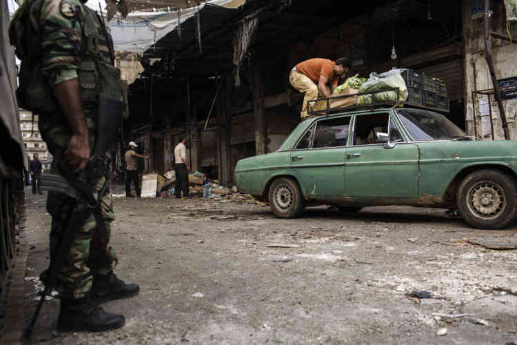 An army guy looks at a local fruit vendor at the Bab el-Tabaneh district in Tripoli. Lebanese soldiers have taken control of a Tripoli neighborhood. Tuesday, October 28, 2014. Diego Ibarra Sánchez for LE MONDE