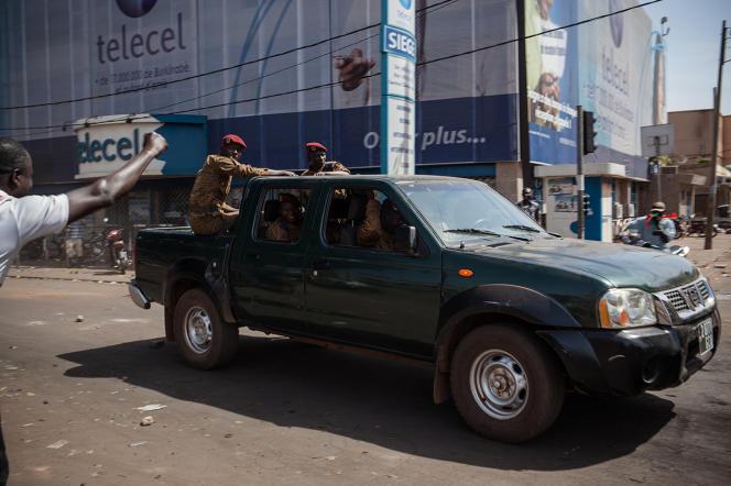 Militaires salués par les manifestants dans une artère du centre-ville de Ouagadougou après l'annonce de la démission de Blaise Compaoré.