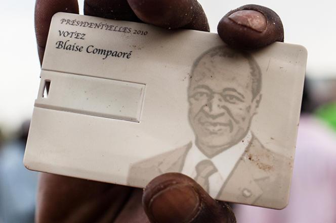 Un jeune montre une carte à l'effigie de Blaise Compaoré qu'il vient de trouver dans la maison de son frère François, après l'annonce de sa démission.