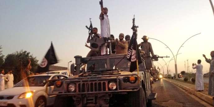 Des hommes de l'organisation Etat islamique paradent dans les rues de Mossoul, en Irak, le 23 juin.