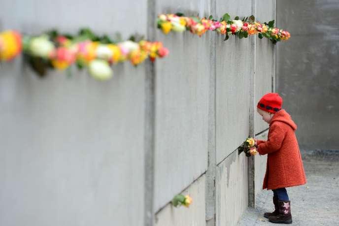 Une petite fille devant le mur de Berlin lors des commémorations du 25ème anniversaire de la chute du mur en novembre 2014. AFP PHOTO / JOHN MACDOUGALL