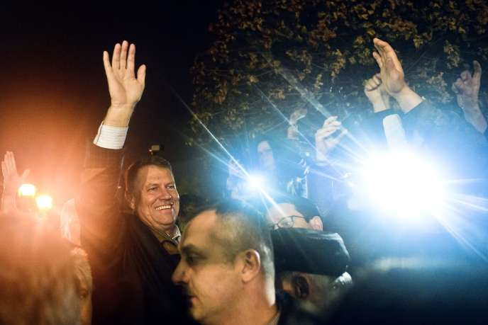 Klaus Iohannis, au centre, salue ses partisans, à Bucarest, dimanche 16novembre.   Klaus Iohannis, leader of Romania's center-right Liberals and mayor of the Transylvanian city of Sibiu, waves to supporters gathered to celebrate his victory in a presidential runoff in Bucharest, Romania, early Monday, Nov. 17, 2014. Romania's Prime Minister Victor Ponta conceded defeat Sunday night in an extremely close presidential runoff against an ethnic German Transylvanian mayor. Ponta had been the favorite to win, but was narrowly edged out by Klaus Iohannis. (AP Photo/Raed Krishan)