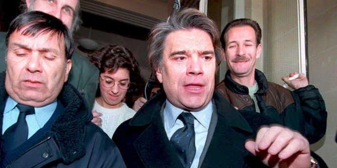 Bernard Tapie quitte le tribunal de commerce de Paris le 14 décembre 1994, après presque quatre heures d'audition par le juge, avec sa femme Dominique, portant sur le Groupe Bernard Tapie (GBT), holding des sociétés de Bernard Tapie, et de Financière et Immobilière Tapie (FIBT) qui contrôle ses biens personnels.