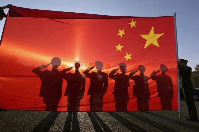 Des policiers à la retraite saluent le drapeau chinois à Pékin le 24 novembre.