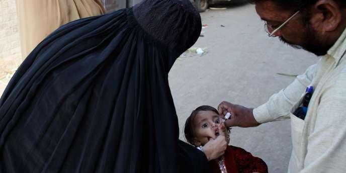 Un médecin pakistanais administre un vaccin contre la polio à un enfant à Lahore, le 11 novembre 2011. Les vaccinateurs sont souvent la cible d'une partie de la population, hostile au vaccin.