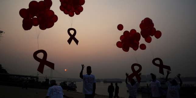 Indian social activists and children release ribbons and balloons during an event to mark World AIDS Day in Kolkata on December 1, 2014. According to the UN AIDS programme, India had the third-largest number of people living with HIV in the world at the end of 2013 and it accounts for more than half of all AIDS-related deaths in the Asia-Pacific region. In 2012, 140,000 people died in India because of AIDS. The Indian government has been providing free antiretroviral drugs for HIV treatment since 2004, but only 50 percent of those eligible for the treatment were getting it in 2012, according to a report by the World Health Organisation. AFP PHOTO/Dibyangshu SARKAR
