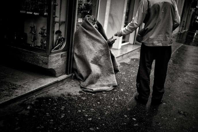«Vous voulez que les pauvres soient des citoyens responsables ? Alors, permettez-leur d'être acteurs de leur avenir !» (Photo: un passant donne une pièce de monnaie à un SDF qui se protège du froid avec une couverture, en décembre 2009 dans une rue du centre ville de Lyon).