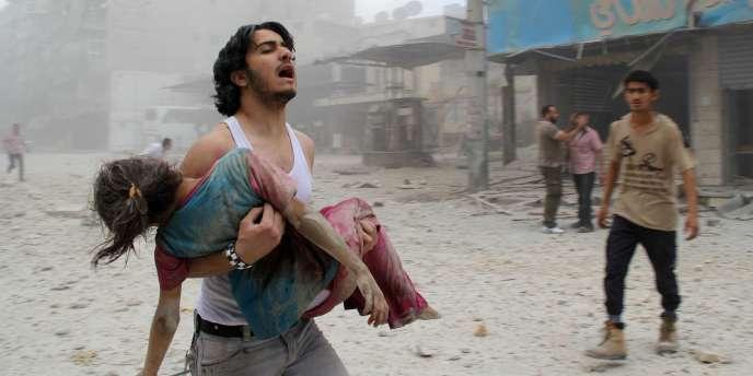 Un homme porte une fillette blessée après une attaque menée par les forces du régime syrien, le 3 juin dernier au nord d'Alep.