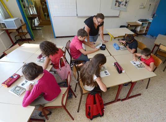 Des écoliers effectuent un exercice de lecture avec Isabelle Coulaud, directrice de  l'école élémentaire Plan de la Cour, à Vitrolles, le 27 août 2012,  lors d'un stage de remise à niveau à destination des élèves présentant, en fin d'école primaire, des difficultés en français et en mathématiques.