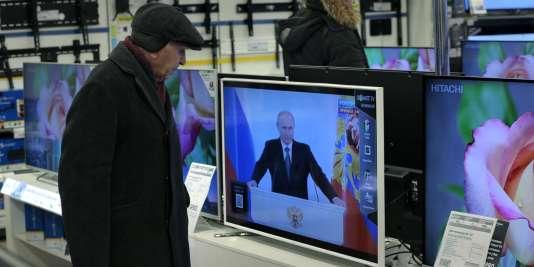 Un client d'une grande surface, à Moscou, regarde l'allocution annuelle du président Vladimir Poutine sur l'état de la nation, en décembre 2014.
