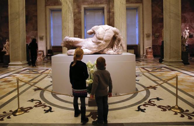 Des visiteurs devant une partie de la frise du Parthénon au Musée de l'Ermitage.