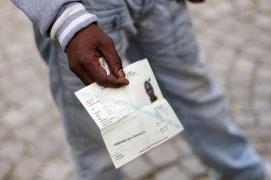 Un réfugié somalien tient le document qui atteste de sa demande d'asile qui ne lui offre pas le droit de travailler.
