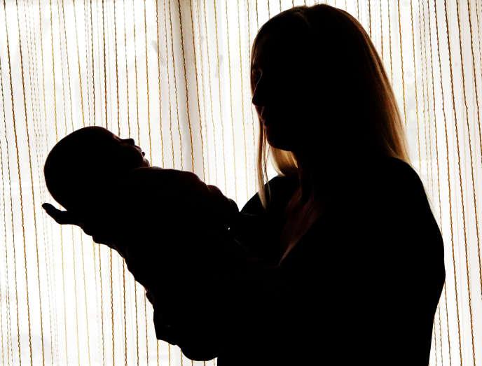 Une mère porte l'une de ses jumelles, nées d'une mère porteuse ukrainienne.