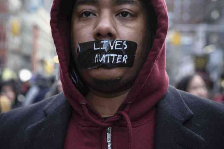 NEW YORK, NY - DECEMBER 13: A man with tape on his mouth marches in the National March Against Police Violence, which was organized by National Action Network, down 14th St on December 13, 2014 in New York City. The march coincided with a march in Washington D.C. and comes on the heels of two grand jury decisions not to indict white police officers in the deaths of two unarmed black men.   Kena Betancur/Getty Images/AFP == FOR NEWSPAPERS, INTERNET, TELCOS & TELEVISION USE ONLY ==