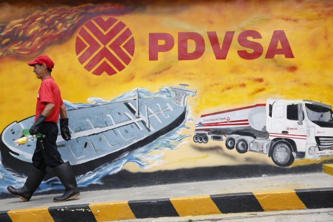 Un travailleur passe devant un mur sur lequel est peint le logo de la compagnie d'Etat Petroleo de Venezuela SA (PDVSA), à Caracas, le 29 août 2014.