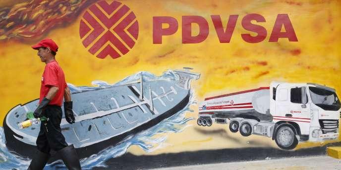Un ouvrier passe devant une fresque murale ornée du logo de PDVSA, Petroleos de Venezuela, la compagnie pétrolière nationale, dans une station service de Caracas, le 29 août 2014.