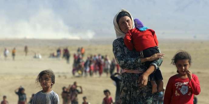 Une mère yézidie fuit la région de Sinjar vers la frontière syrienne, à travers un corridor ouvert par le Parti des travailleurs du kurdistan (PKK), le 11août2014.