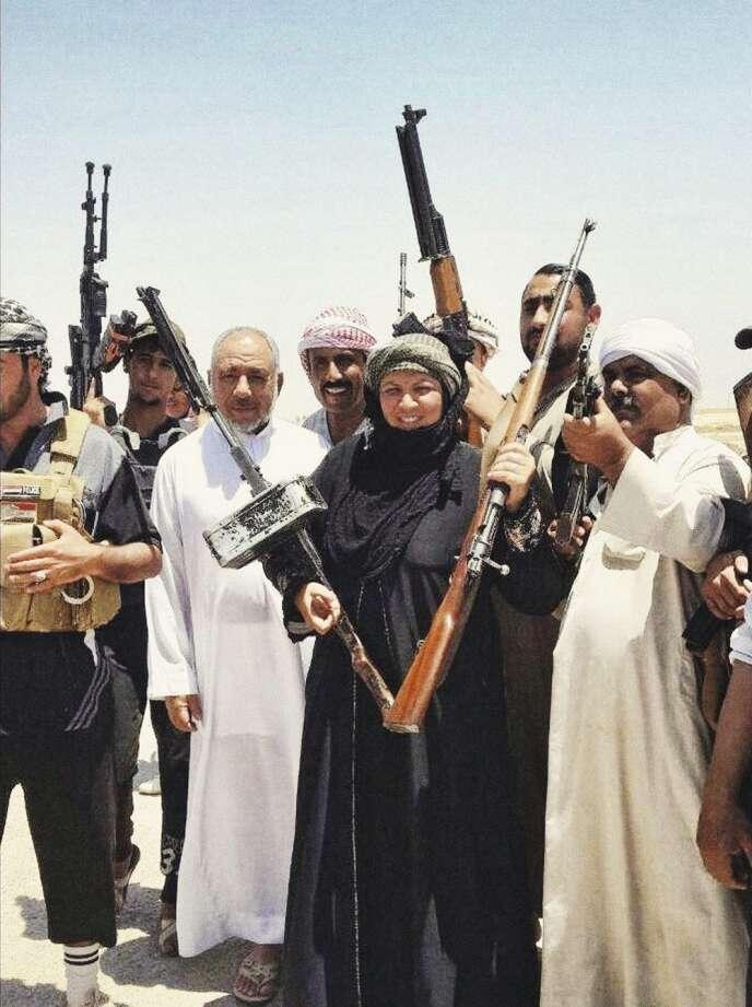 Omaya Al-Jbara fait le V de la victoire avec des combattants d'Al-Alam.