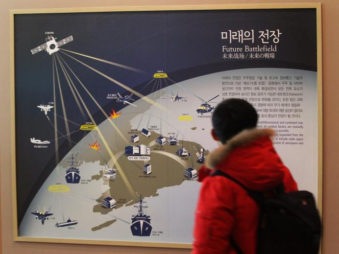 Un étudiant sud-coréen devant une affiche sur la cyberguerre dans la péninsule coréenne à Séoul, le 23 décembre.