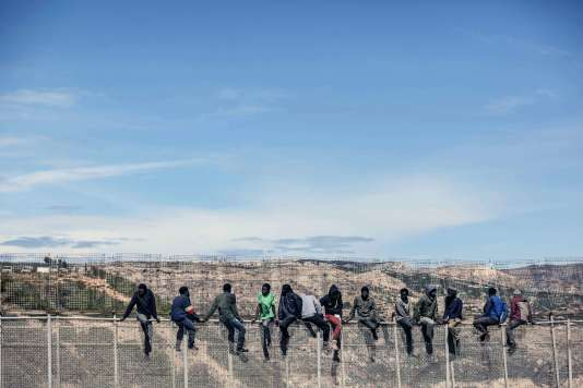 Des candidats à l'immigration en Europe patientent en haut d'un grillage entre le Maroc et l'enclave espagnole de Melilla, en 2014.