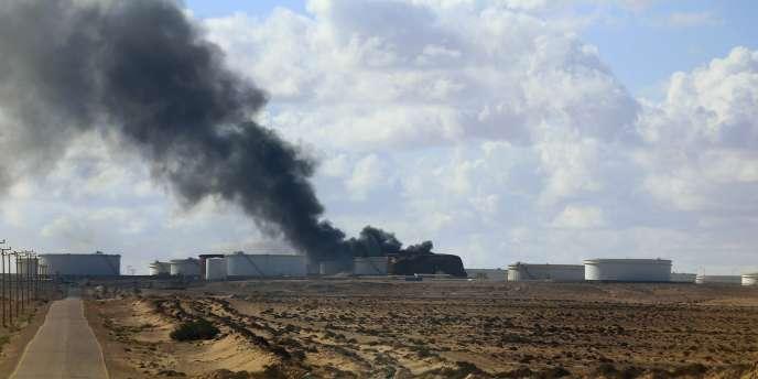 De la fumée sort d'un réservoir pétrolier en feu dans le terminal d'Al-Sedra en Libye.