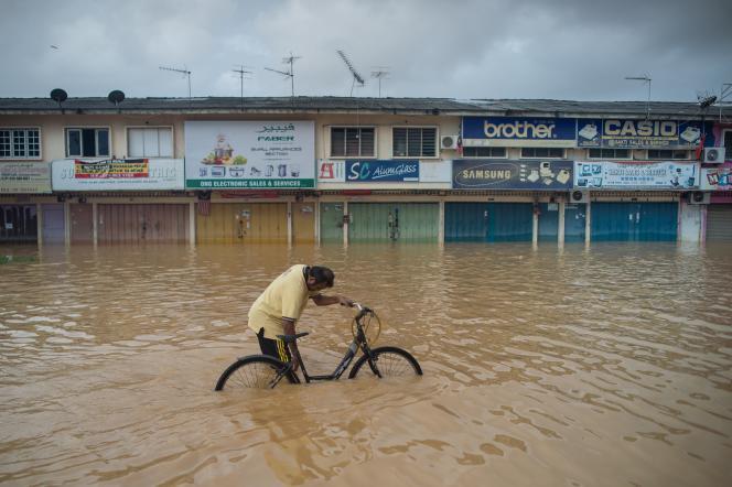 Un homme pousse sa bicyclette à Kota Bahru, le 28 décembre.