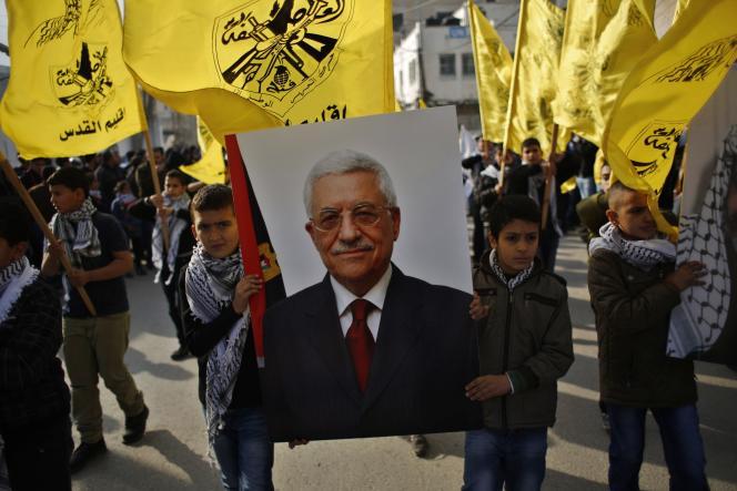 Des manifestants brandissent le portrait du président de l'Autorité palestinienne, Mahmoude Abbas, le 1er janvier près de Ramallah, pour célébrer le 50e anniversaire de la création du Fatah.