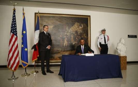 L'ancien président américain Barack Obama signe un livre de condoléances après l'attentat contre la rédaction de « Charlie hebdo», à côté de l'ambassadeur de France Gérard Araud, le 8 janvier 2015.