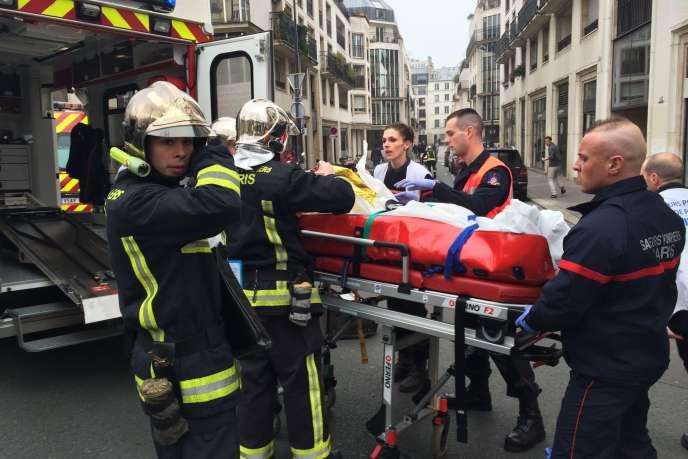 Des pompiers évacuent une victime devant le siège de Charlie Hebdo, à Paris.