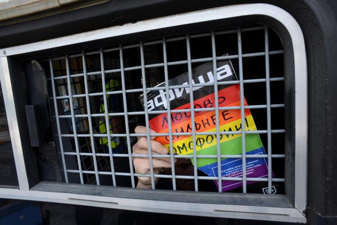 Un militant arrêté pour avoir participé à une marche pour les droits des homosexuels interdite brandit une pancarte proclamant