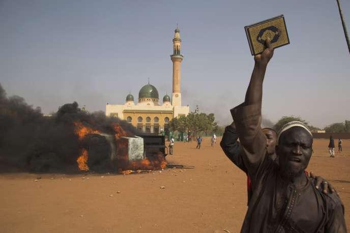 Homme brandissant le Coran au Niger pour protester contre