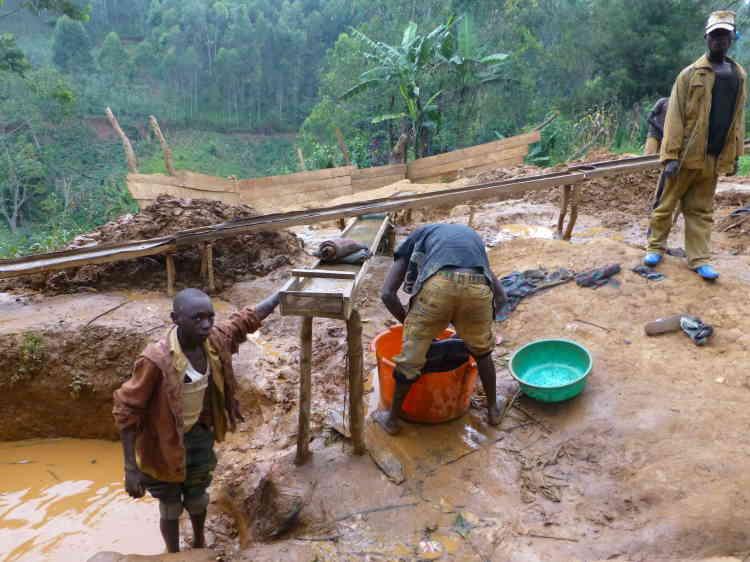 Des enfants nettoyant et tamisant des résidus miniers, à la recherche d'or.