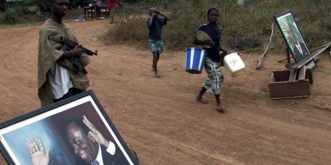Un soldat de la rébellion du Mouvement pour la Justice et la Paix a disposé un portrait de Félix Houphouët-Boigny au checkpoint de Facobli, près de Man, en 2003.