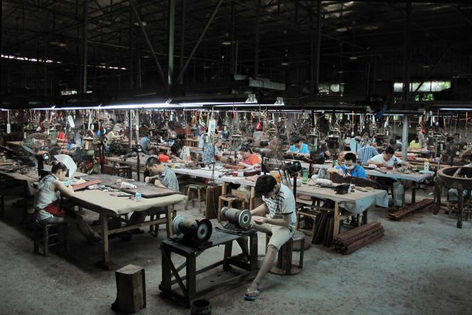 Des ouvriers sculptent des panneaux de bois de rose dans l'un des ateliers de Sanfu Classical Craft Furniture, le principal fabricant de meubles de Xianyou.
