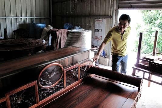 Dans son magasin, Li Sheng Peng, directeur de Yimu Xian Ju, montre un lit fabriqué en bois de rose de Madagascar.