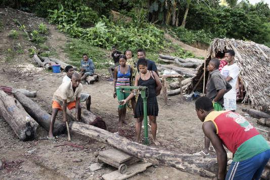 """A l'entrée du village d'Antanandavehely, une femme qui travaille pour le compte des """"barons"""" du bois de rose procède à la pesée des troncs qui seront ensuite acheminés vers la côte."""