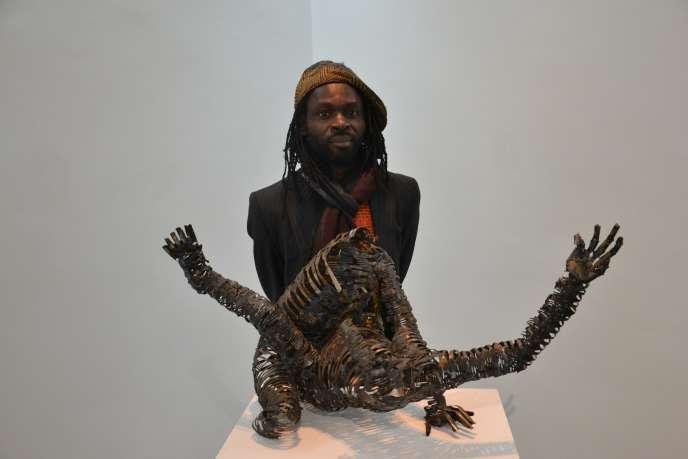 L'artiste congolais Freddy Tsimba devant une de ses sculptures représentant une femme victime de viol.