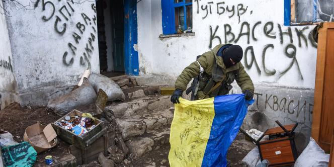 Un rebelle pro-russe tient un drapeau ukrainien dans la ville de Krasniy Partizan.